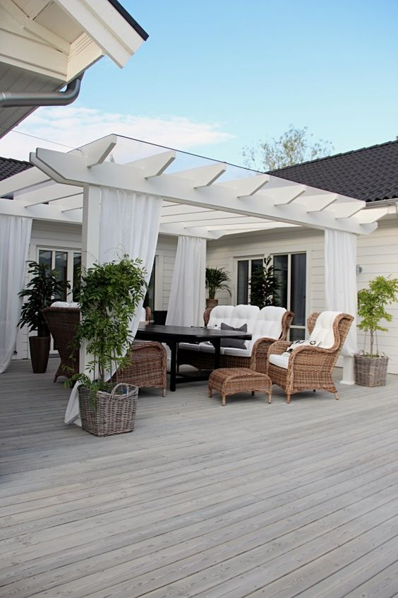 очаровательная белая беседка на палубе с плетёной мебелью.